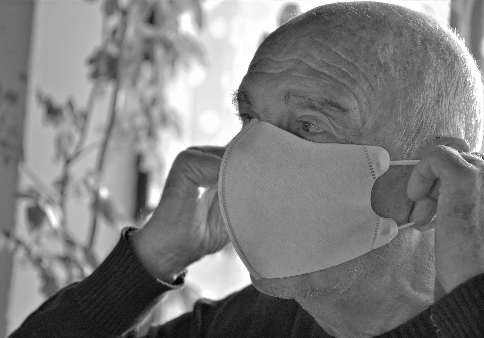 Elderly man putting on mask.