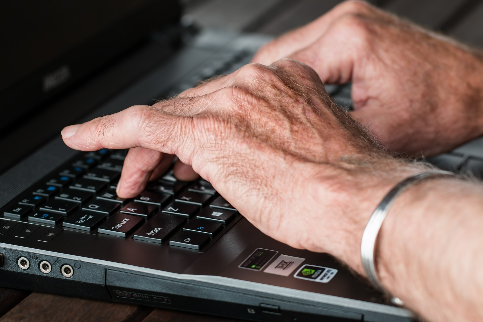 older hands typing on a computer keyboard