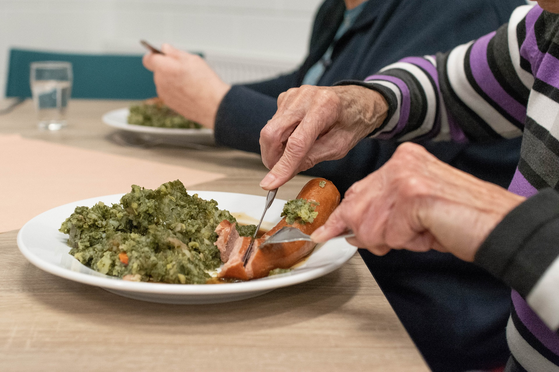 Hands of an older woman eating a meal